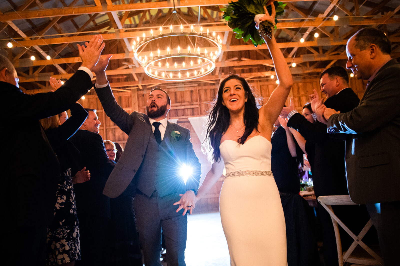 Bride and groom giving high-5's while entering their wedding reception
