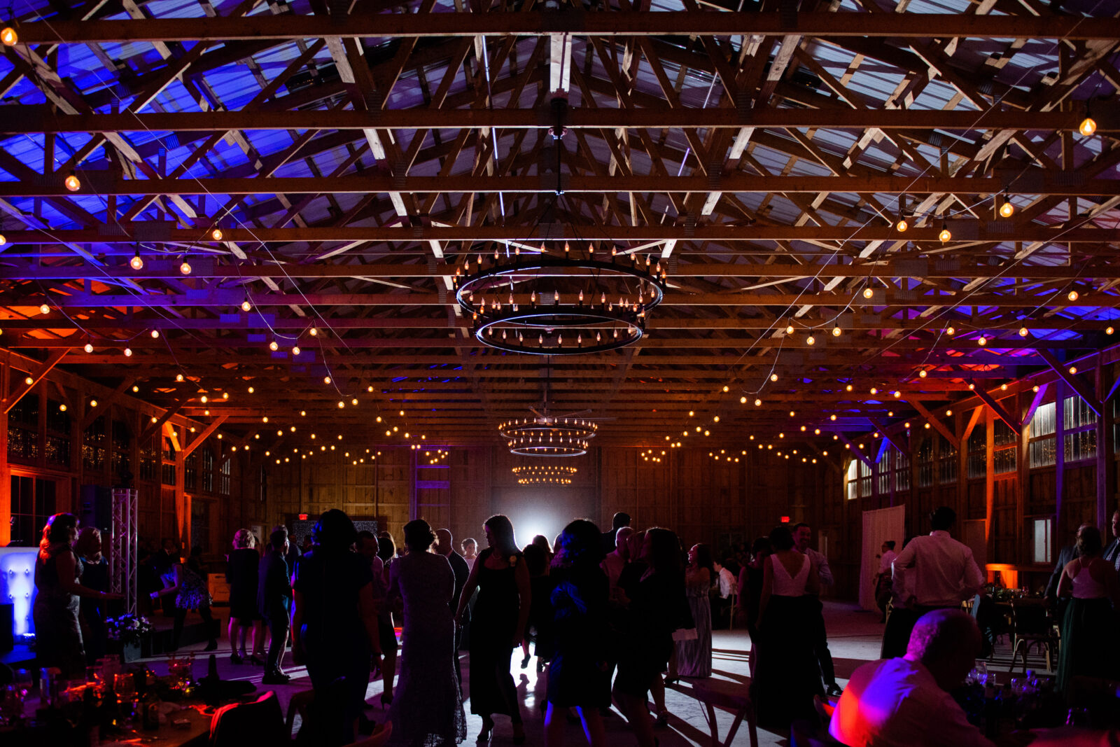 Wide angle of a moody wedding reception with blue, red, and purple lighting filling the room