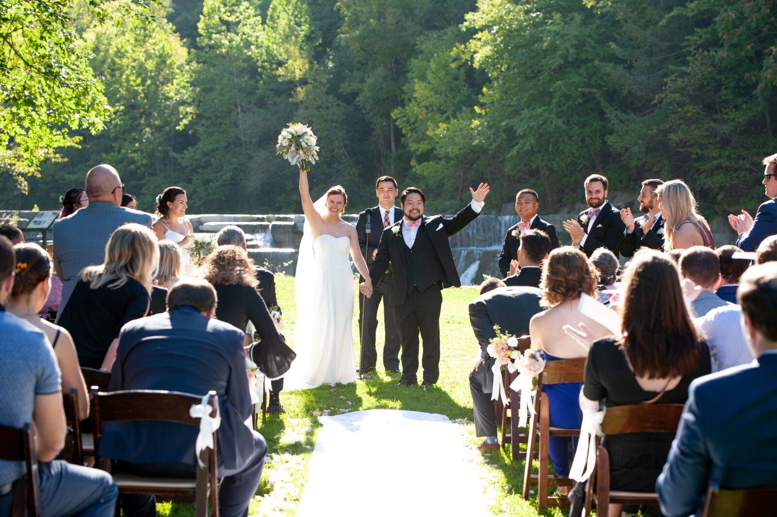 A bride and groom cheer with their wedding attendees