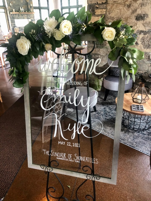 """A sign decorate with white flowers that says """"Welcome Emily and Kyle"""""""